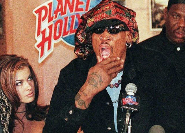Carmen Electra looking at Dennis Rodman as he makes a speech at a podium.