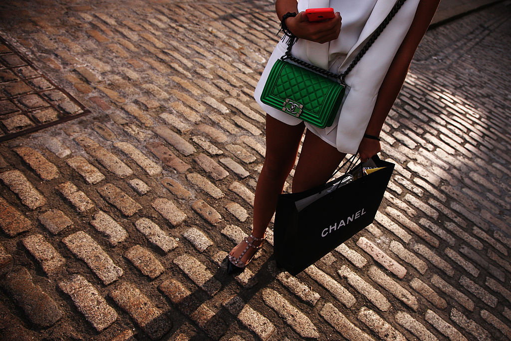 woman carrying chanel shopping bag