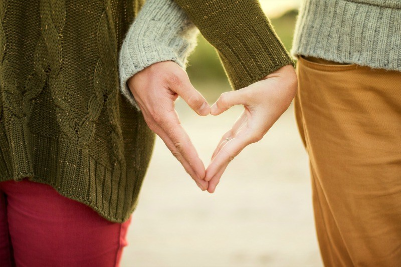 a couple making heart shaped hands