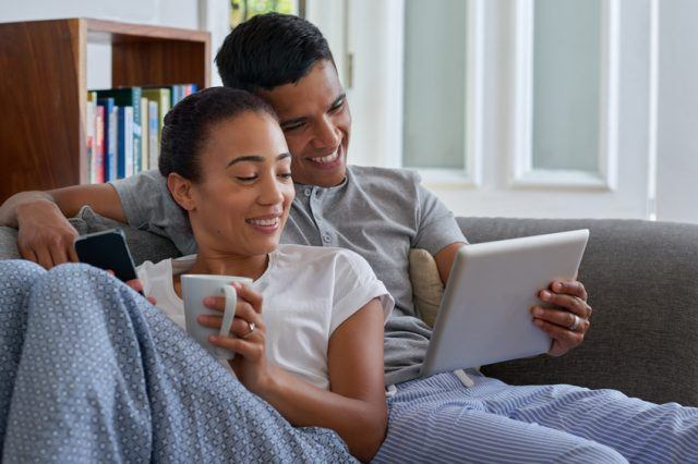 A smiling couple cuddles on the sofa while looking at a tablet computer