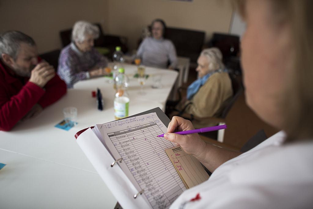 a nurse takes notes as senior patients sit