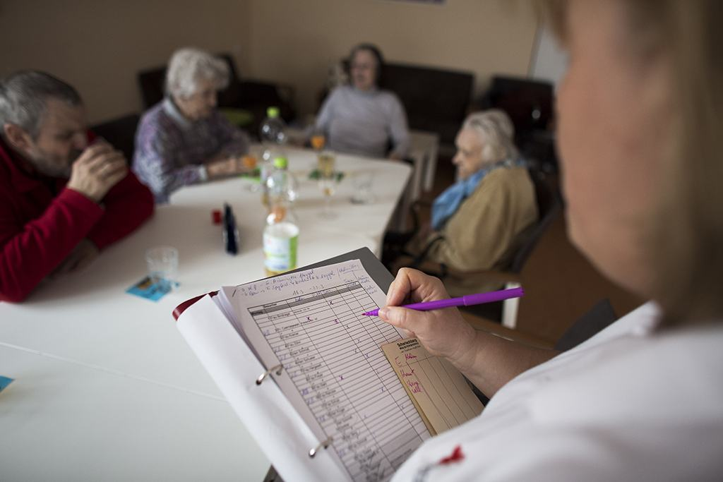 A nurse takes notes as elderly patients sit at a table