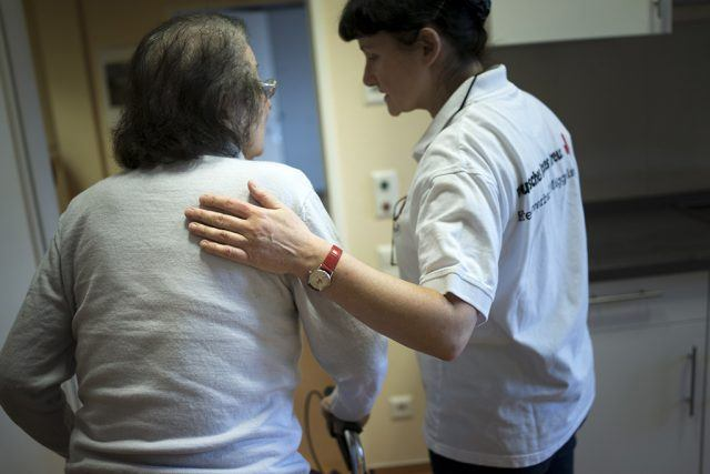 caregiver assisting a woman with a walker