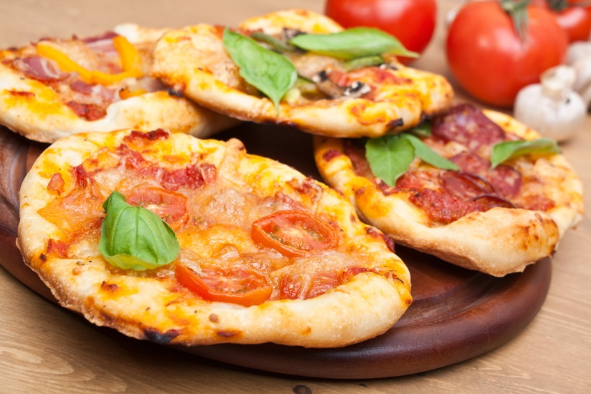 small pizzas and engredients on a table