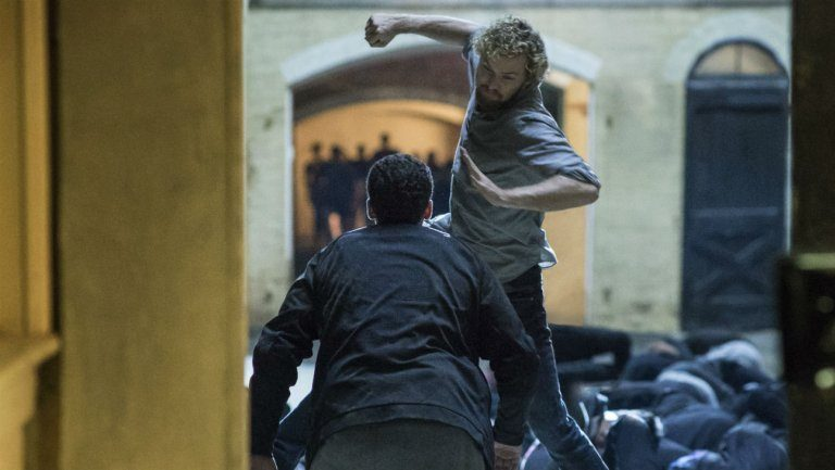 Finn Jones in mid-jump about to punch a man in a suit in Iron Fist