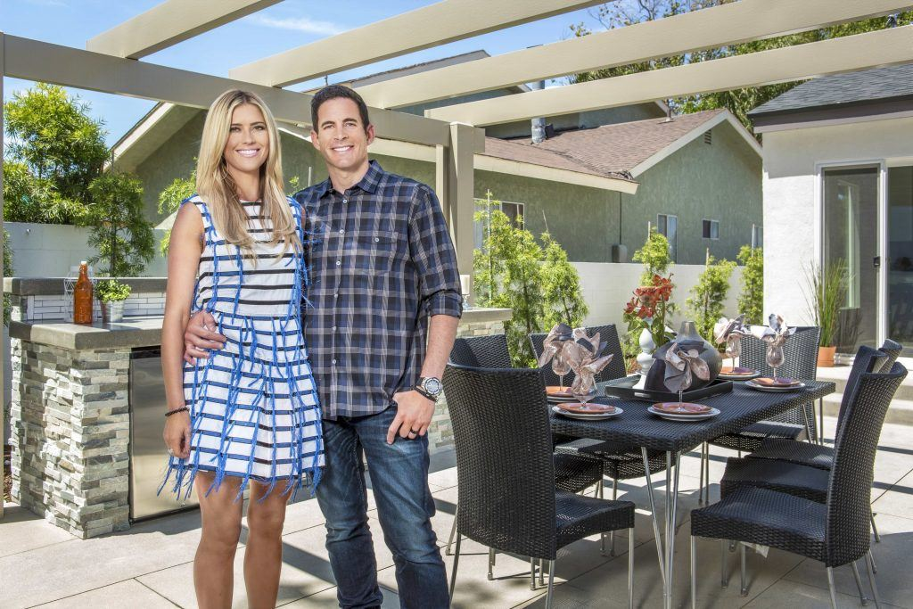 Christina and Tarek El Moussa of Flip or Flop standing in front of a house