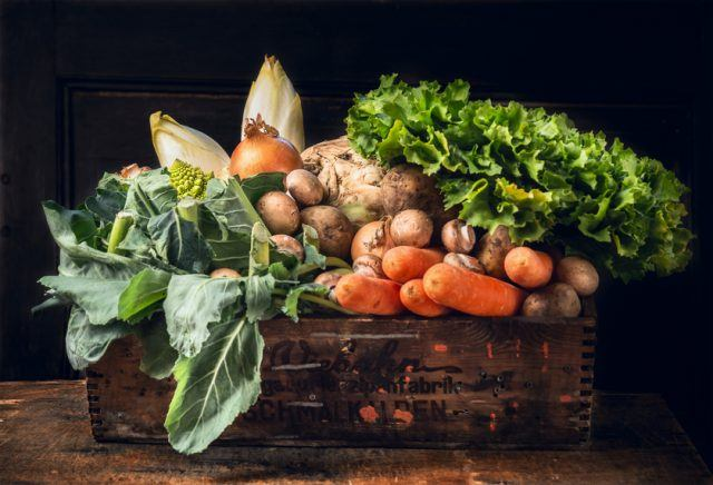 Various fresh vegetables in a wooden crate.