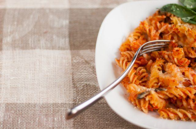 Fusilli pasta bolognese on a white plate on a table with a fork.