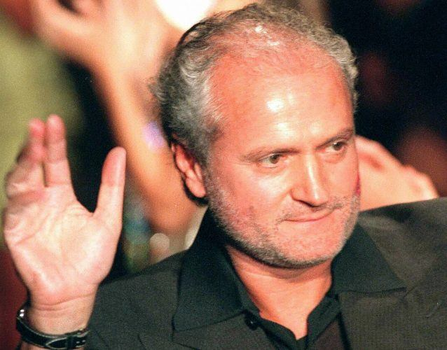 Gianni Versace waving at a crowd during a fashion show.