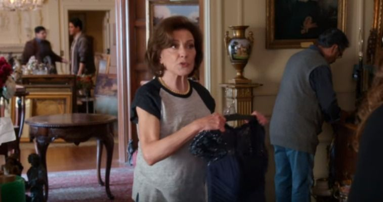 Woman in a t-shirt holding a dress in a nice house in Gilmore Girls: A Year in the Life