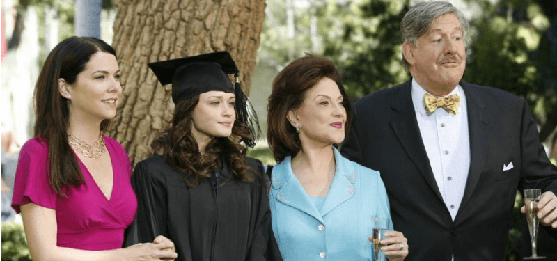 Lauren Graham as Lorelai Gilmore, Alexis Bledel as Rory Gilmore, Kelly Bishop as Emily Gilmore, and Edward Herrmann as Richard Gilmore standing outside next to a tree on Gilmore Girls