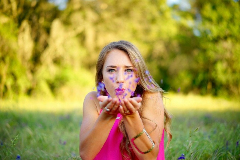 girl blowing flower petals