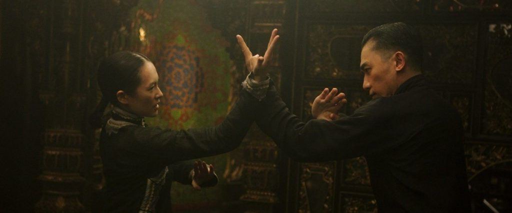 A man and a woman fight, with their arms crossed and hands out