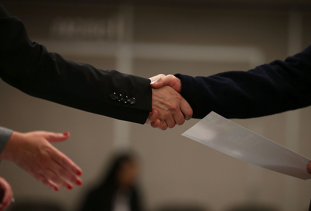A job seeker shakes hands with a recruiter