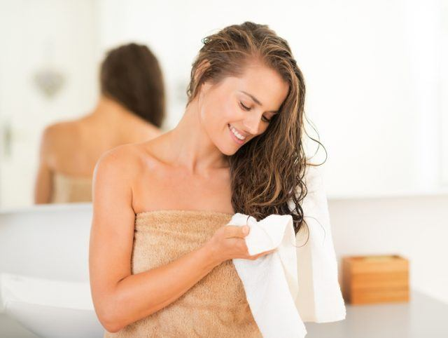 young woman wiping hair with towel