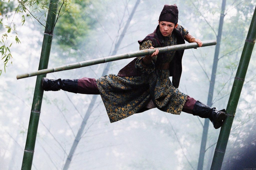 A woman balancing on two large bamboo stalks, holding a pole out in front of her for balance
