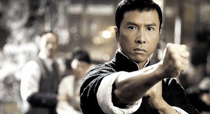Donnie Yen looking at the camera, with his right fist pointed out