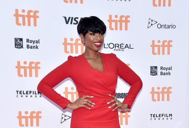 Jennifer Hudson attending a premiere, poses in a red dress.