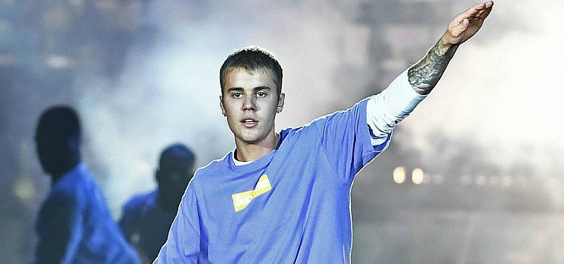 Justin Bieber is onstage with one arm up in the air.