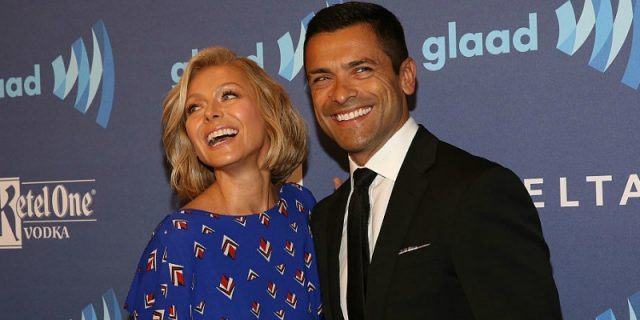 Kelly Ripa and Mark Consuelos laughing while posing for the paparazzi.