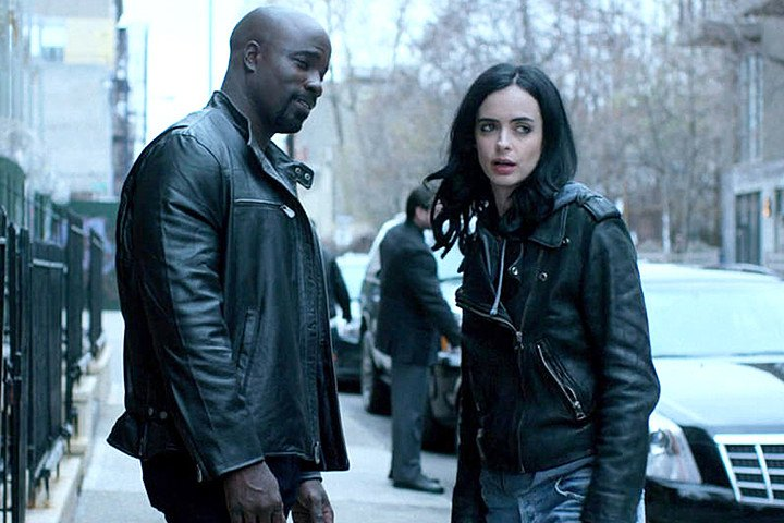 Luke Cage wearing a leather jacket, next to Jessica Jones in a similar jacket