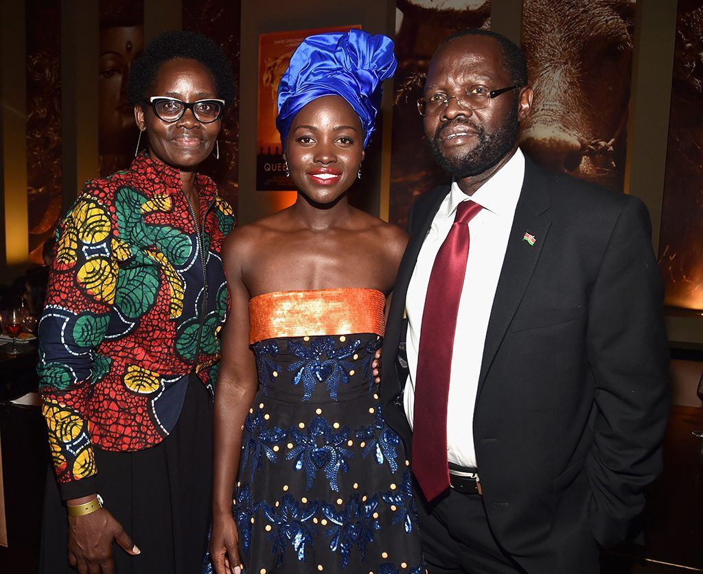 Lupita Nyong'o attending a movie premiere standing next to her parents