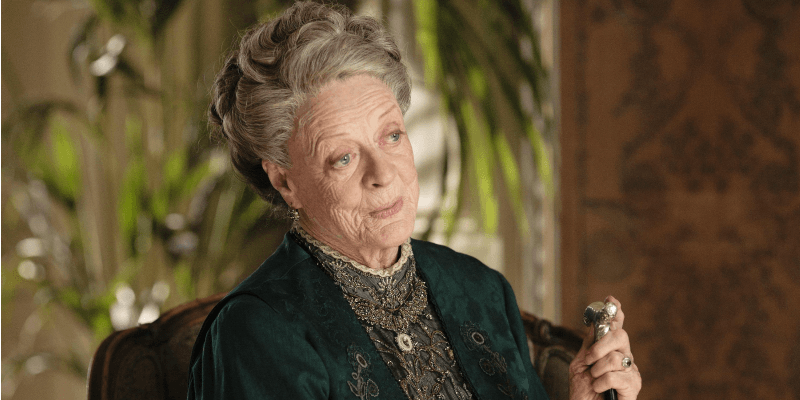 Maggie Smith sits in a chair in a scene from Downton Abbey