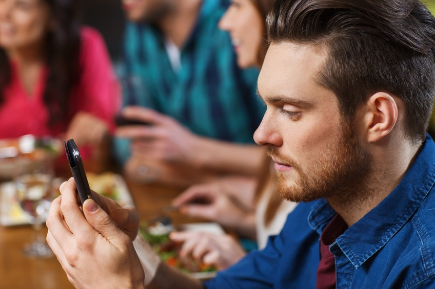 Man with smartphone sitting at a table with friends.