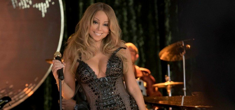 Mariah Carey is smiling in a black body suit.