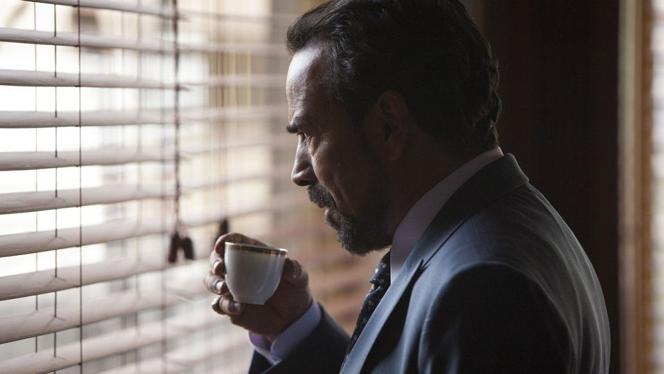 A man holds an espresso in his hand while looking out the window in Narcos Season 2