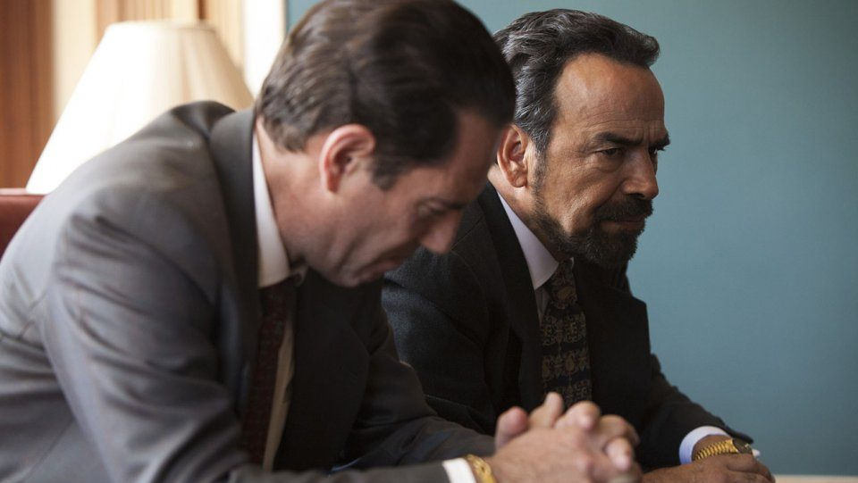 Two men in suits sit next to each other with their hands clasped in Narcos Season 2
