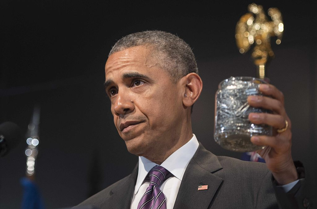President Barack Obama holds up a jar of collected paperclips