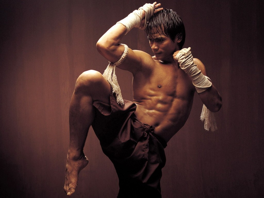 A shirtless Tony Jaa balancing on one foot with his fists raised to fight