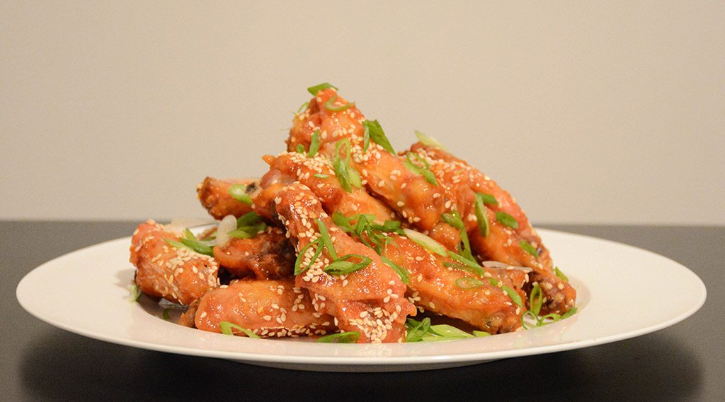 profile of a plate of orange-sesame chicken wings