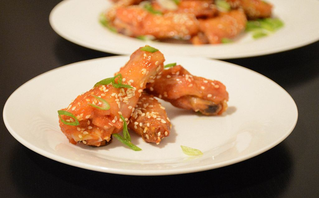a small plate filled with orange-sesame chicken wings