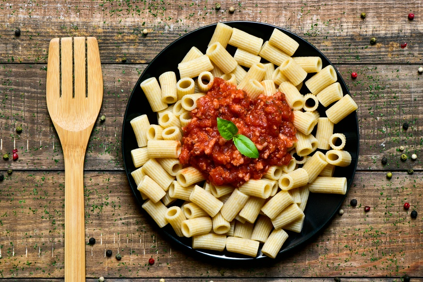 penne rigate with bolognese sauce and wooden fork