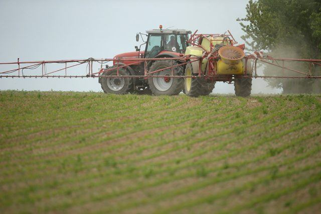 A tractor spraying pesticides on crops.
