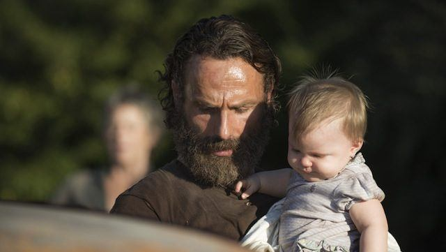 Rick (Andrew Lincoln) carries baby Judith in a scene from the fifth season of 'The Walking Dead'