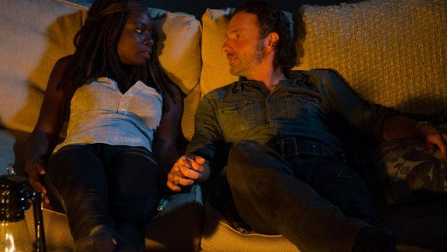 Michonne and Rick holding hands on the couch in a scene from 'The Walking Dead' episode 'The Next World'