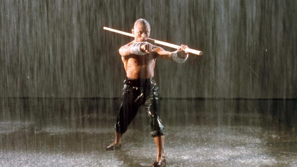 A shirtless man in the rain, holding a long staff over his shoulder, with his other fist pointed out