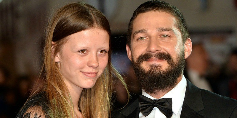 Shia LaBeouf and wife, Mia Goth are smiling on the red carpet.