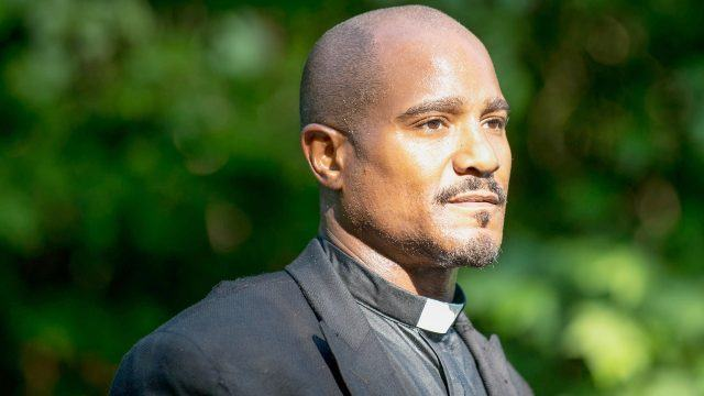Father Gabriel (Seth Gilliam), looking off to the right of the frame