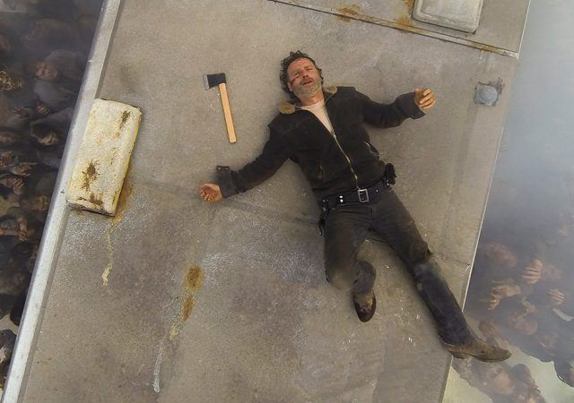 Rick laying on top of an RV, with his arms splayed out and an ax sitting next to him