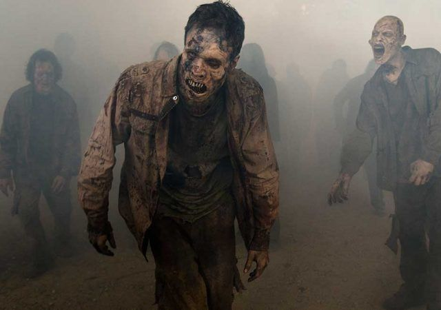 Zombies walk out of the fog in a scene from Season 7 of 'The Walking Dead'