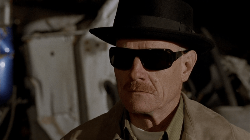 Walter White, wearing sunglasses and a porkpie hat, looking to the left of the frame