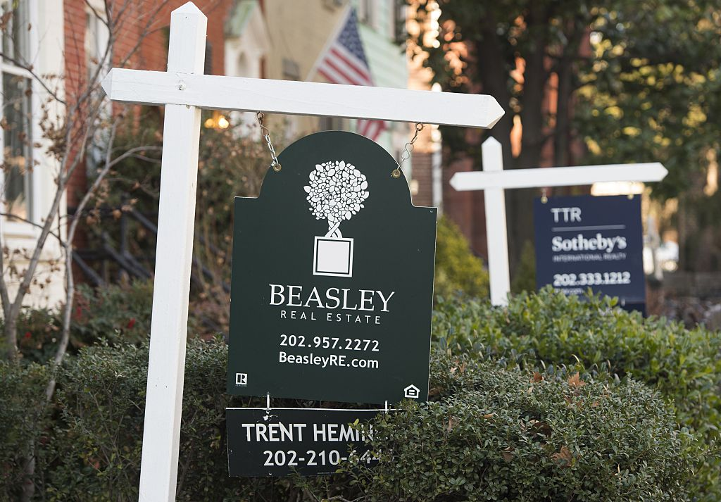 Real estate for sale signs are seen in front of homes for sale