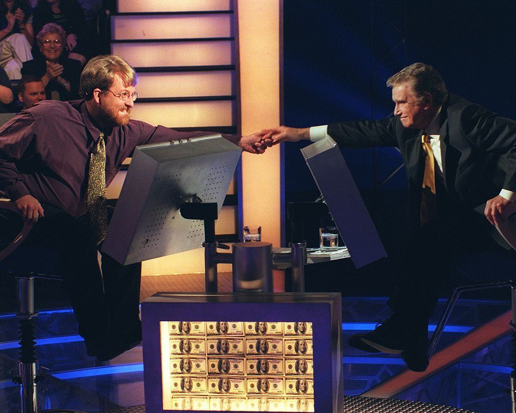 Contestant Doug Van Gundy shakes the hand of host Regis Philbin as they sit in front of their monitors on Who Wants to Be a Millionaire
