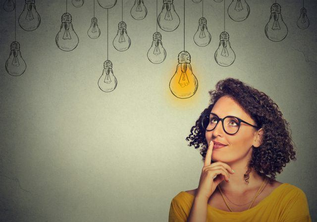woman in glasses looking up to drawings of lightbulbs