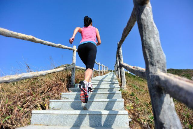 A woman running up mountain stairs.