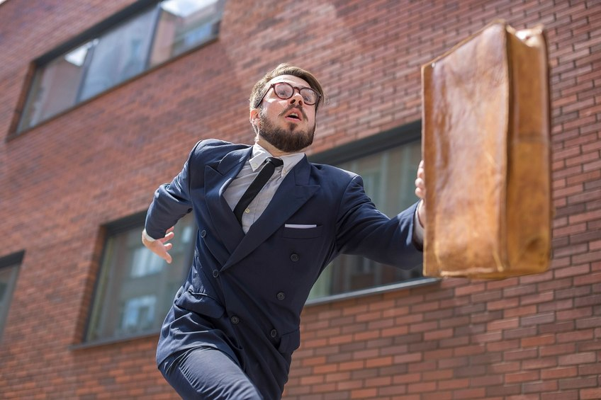 Young businessman with a briefcase and glasses running